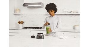 Ninja Foodi Power Nutri Blender 2in1 CB100UK InUse Cup BW GreenPuttingLidOn RT CMYK r